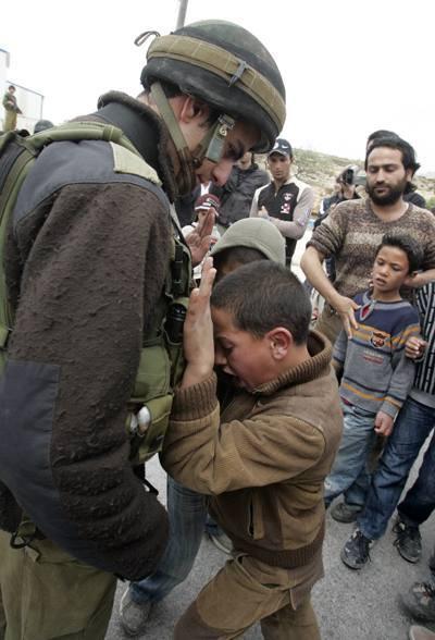 Palestinian boy resisting a soldier