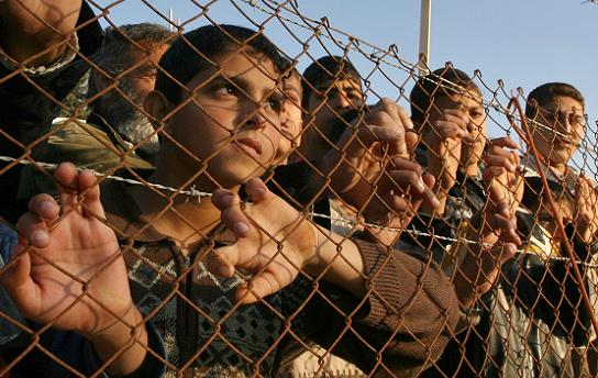 Palestinian Children watching an Israeli Soldier from behind barbed wire